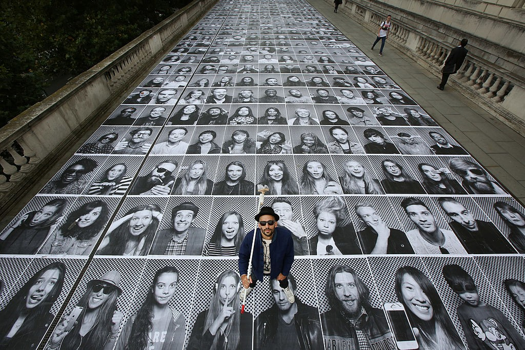 LONDON, ENGLAND - OCTOBER 07: French artist 'JR' poses with some of his giant portraits at Somerset House for his Inside Out project on October 7, 2013 in London, England. Displaying at the Lazarides gallery and also on hoardings at a building site opposite the Old Bailey, the exhibition is comprised of giant black and white images of members of the public who are photographed in a mobile studio mounted on the back of a small truck. The Inside Out photo booth truck is located on the River Terrace of Somerset House from 3rd - 11th October 2013. (Photo by Peter Macdiarmid/Getty Images)